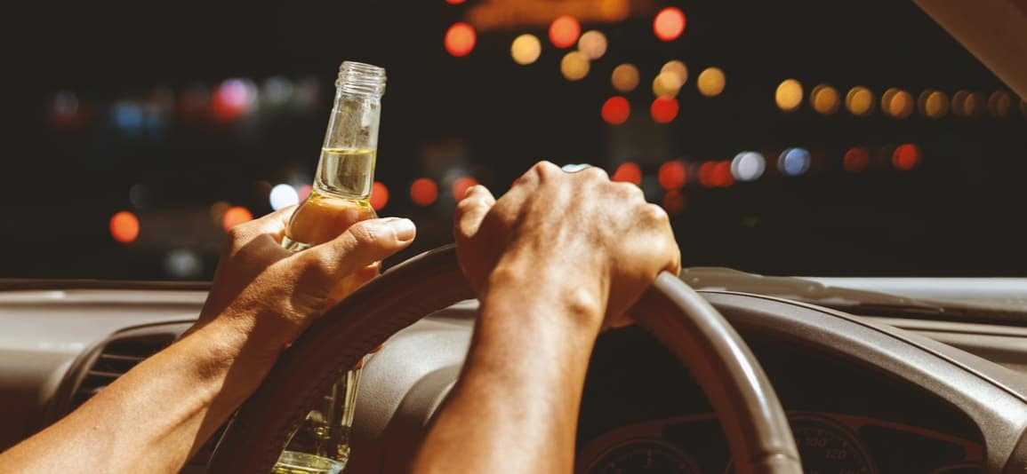 driver drinking behind the wheel about to cause an auto accident