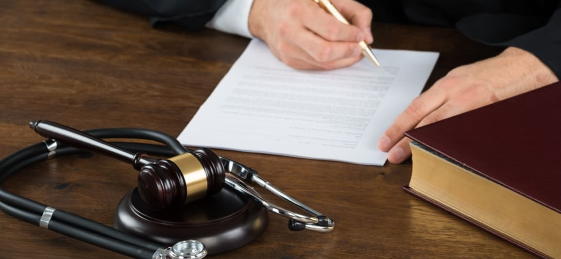 attorney reviewing questions about a medical malpractice case near a gavel and stethoscope