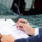 Man filling out an accident report after a car crash