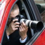 Personal injury law firm investigator taking photos from vehicle window
