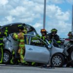 Broward County emergency services rescuing car accident victim from damaged vehicle
