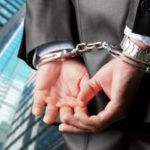 Personal injury attorney with both hands handcuffed behind his back after committing an ethics violation