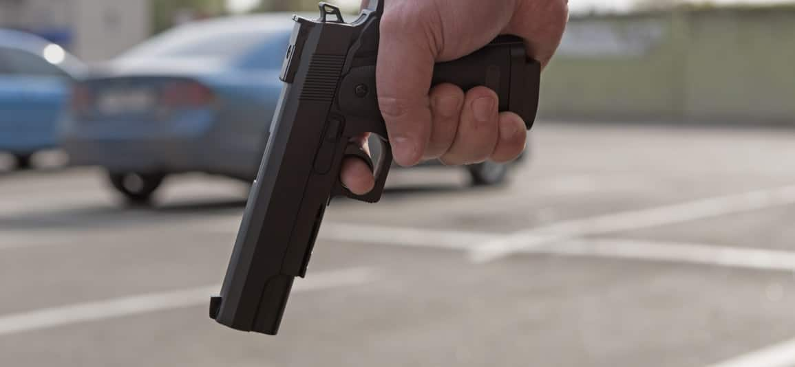 man holding a firearm before being arrested for weapons charge