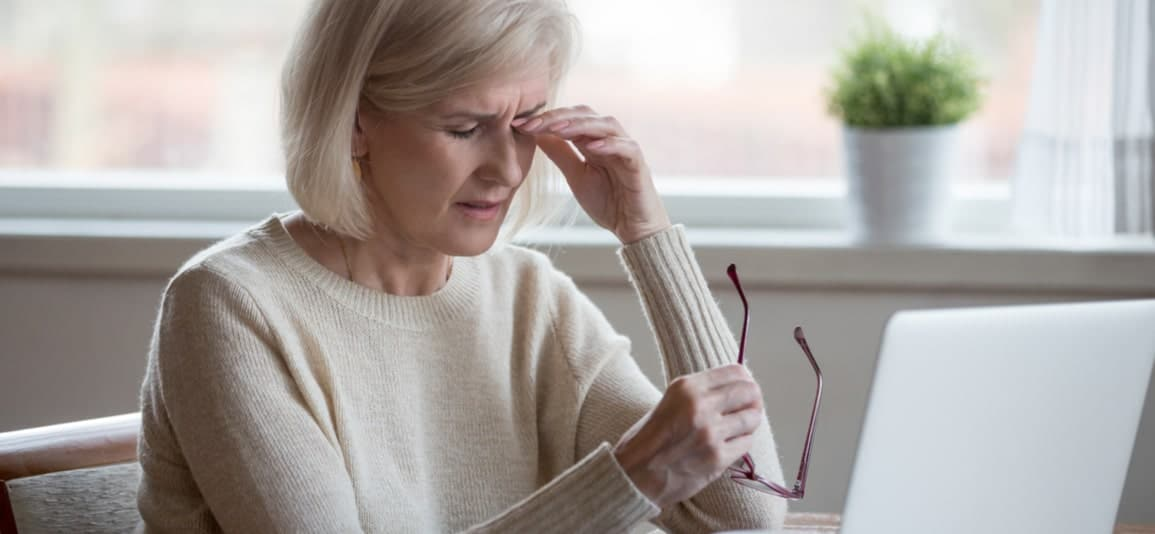 Older woman with hand on head suffering from vision loss
