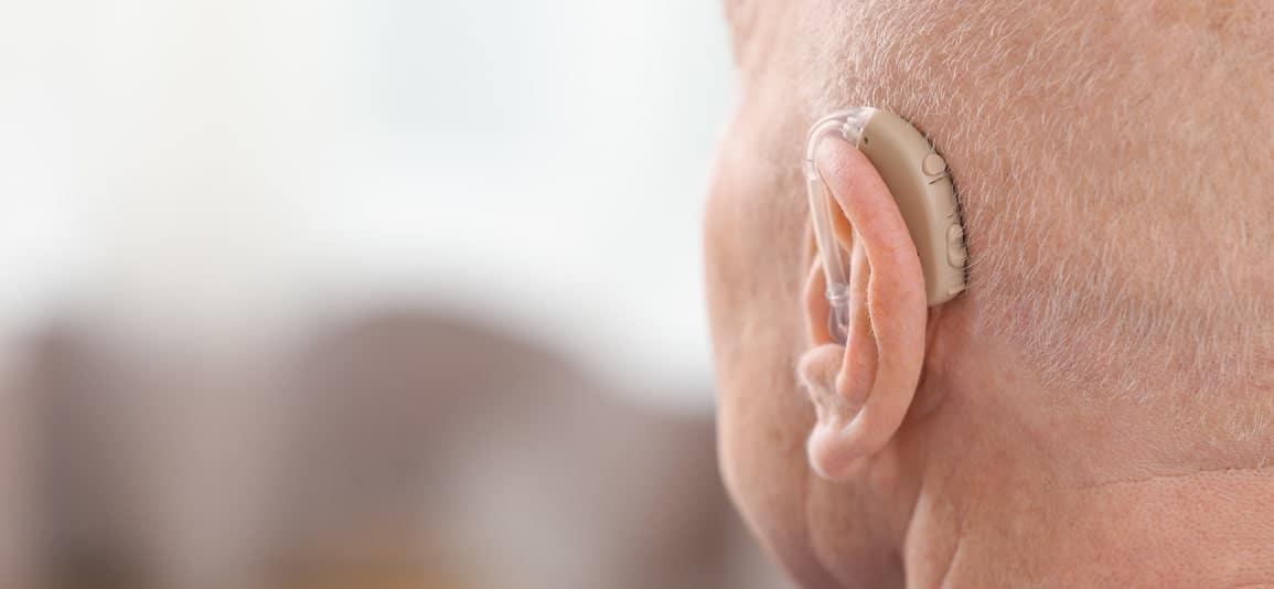 a man wearing a hearing aid due to hearing loss injury