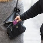 Man stealing a purple wallet out of a black purse on a woman's shoulder.