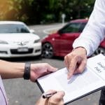 Insurance adjuster pointing to place to sign on insurance documents